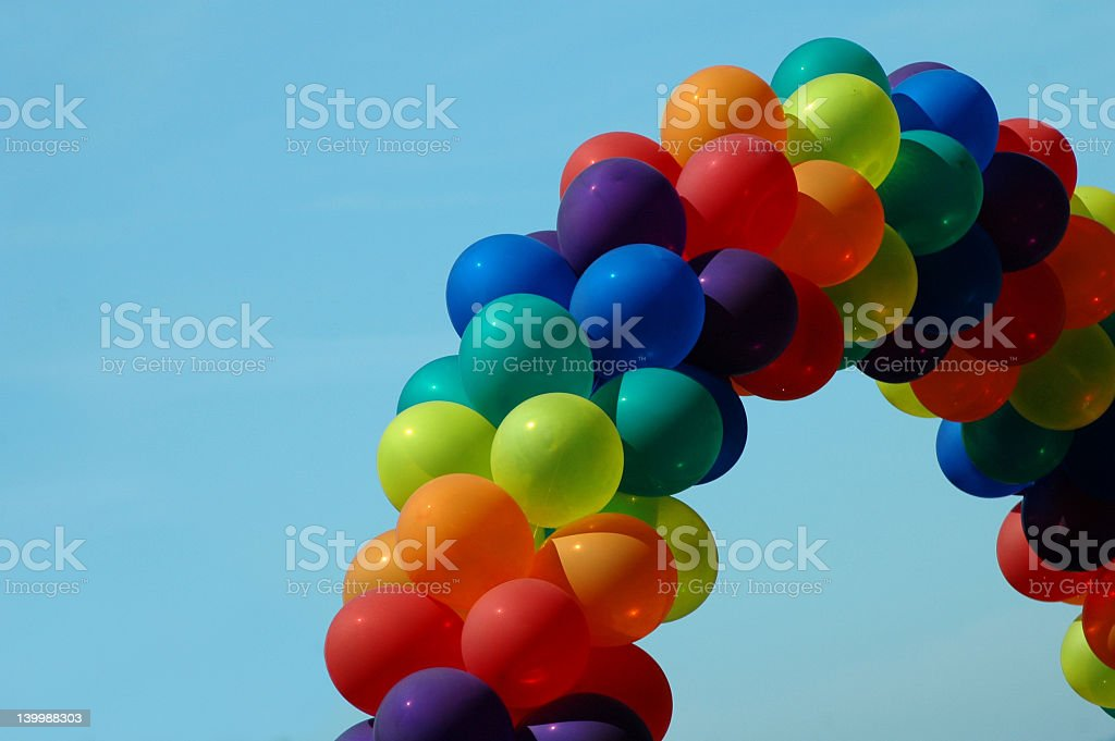 Arch of rainbow balloons in front of blue sky stock photo