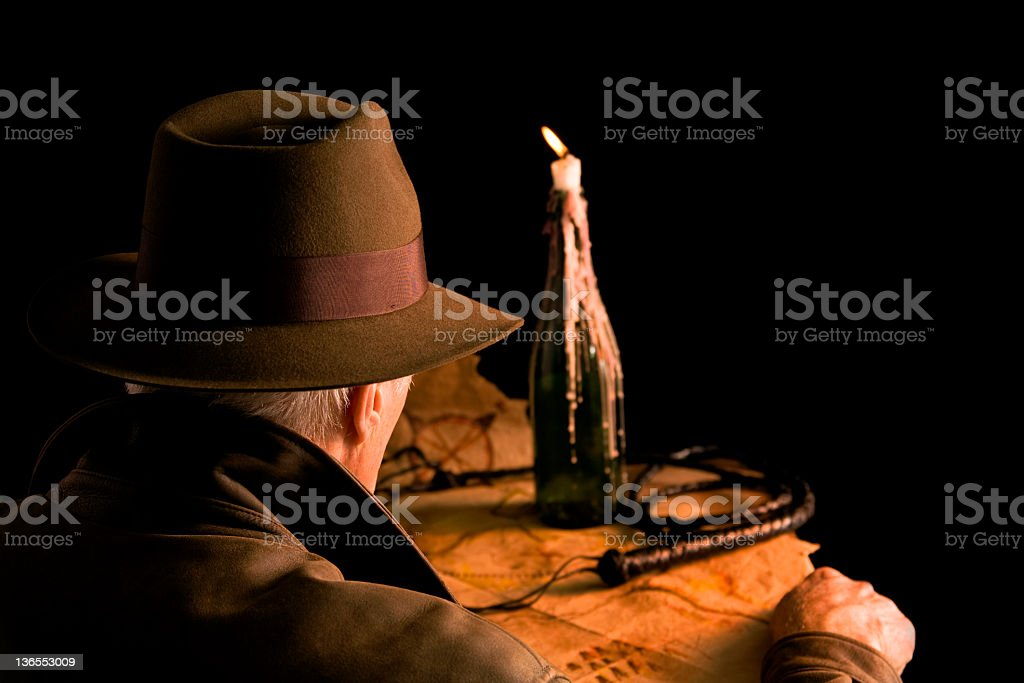 Archaeologist. Adventure. Old-fashioned. Man brown leather coat, felt hat, map. stock photo