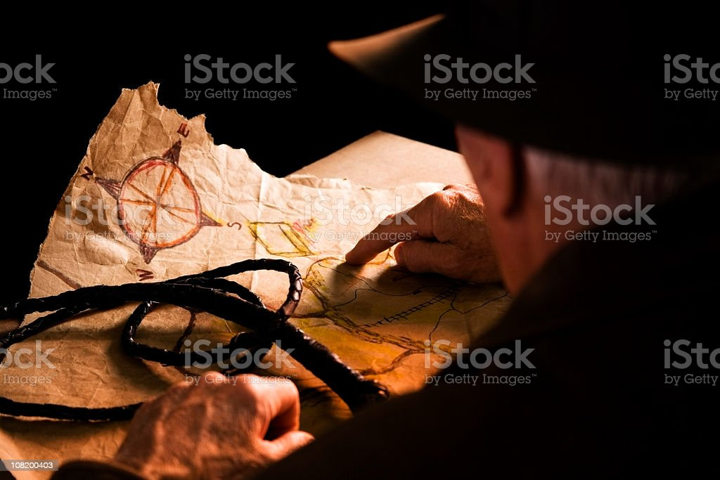 Archaeologist. Adventure. Old-fashioned. Man brown leather whip, felt hat, map. royalty-free stock photo