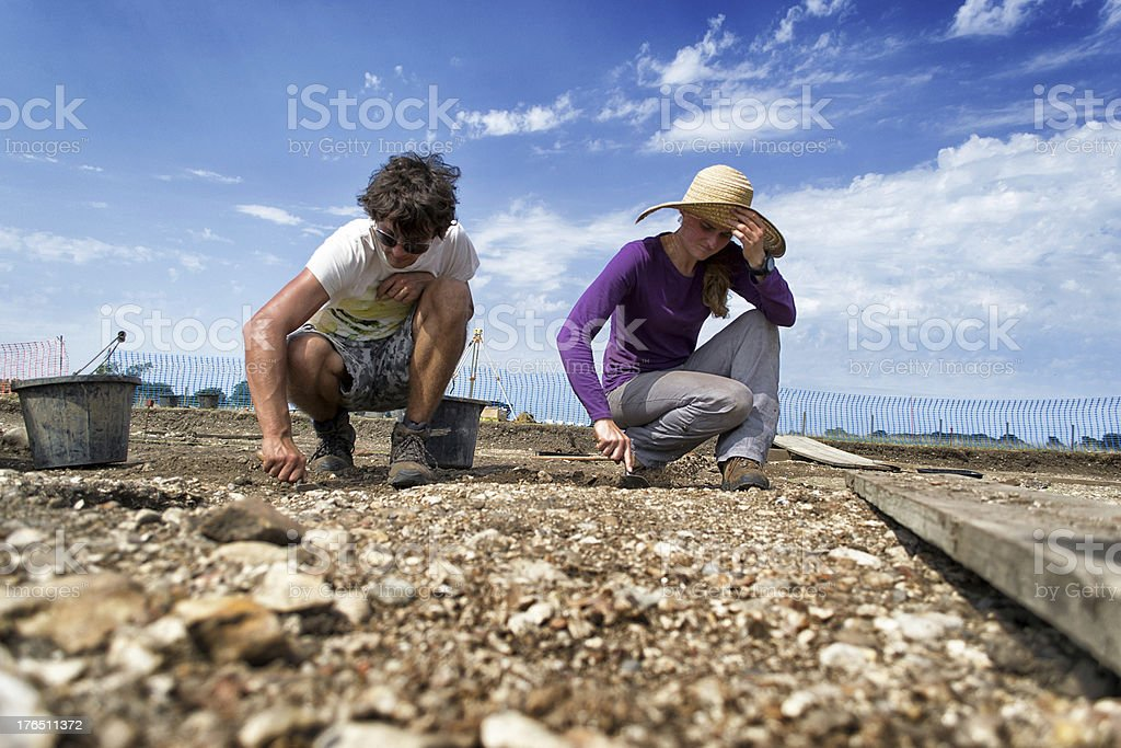 Archaeologist and student excavating stock photo