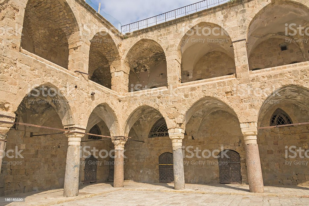 Arched gallery of Khan al-Umdan viewed from paved courtyard royalty-free stock photo