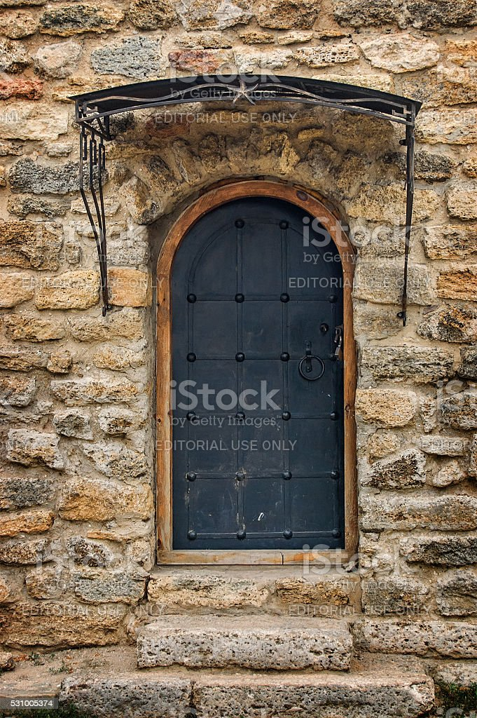 Arched medieval wooden door in a stone wall stock photo