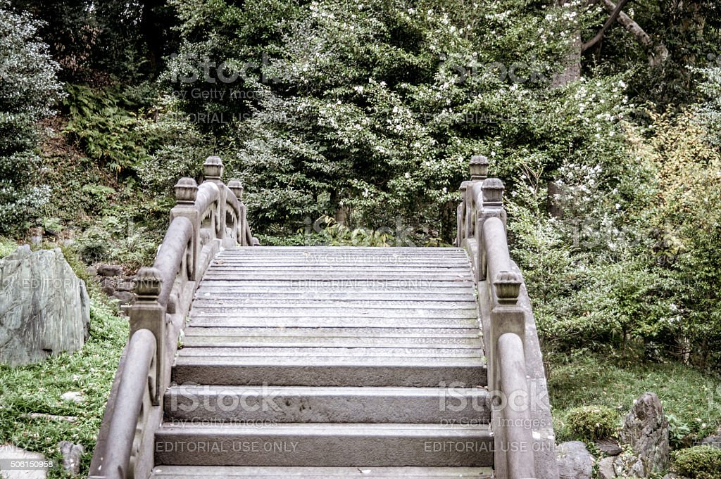 arched stone bridge in japanese garden royalty free stock photo