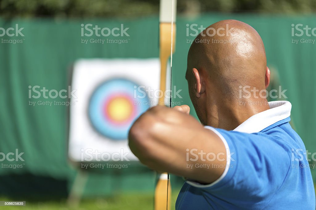Archer aiming at target with bow and arrow stock photo
