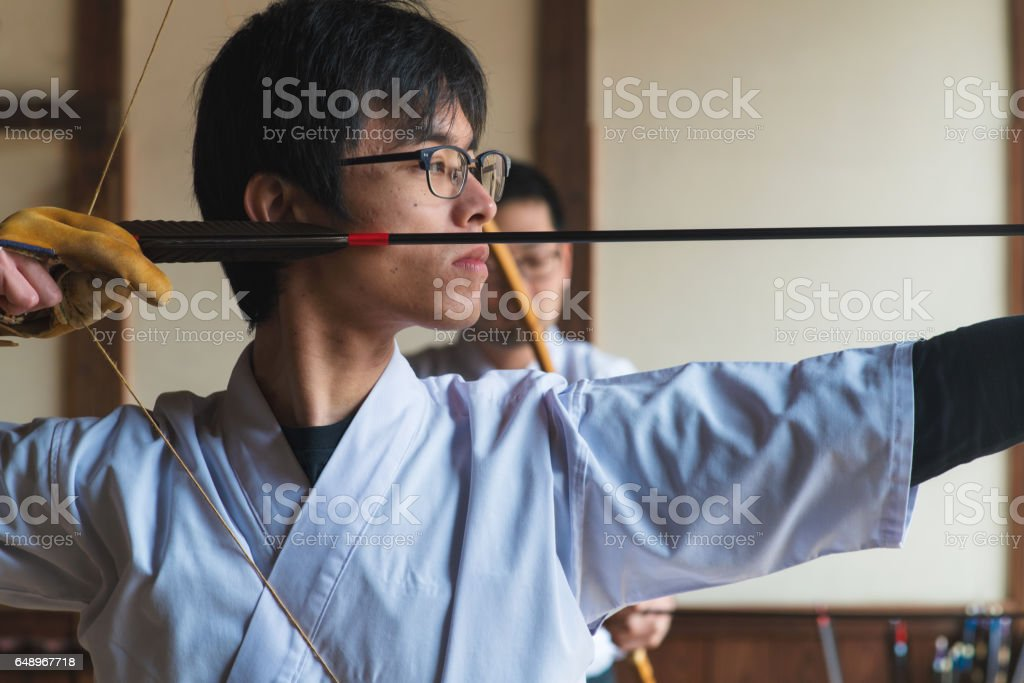 Archer draws his bow, ready to fire stock photo