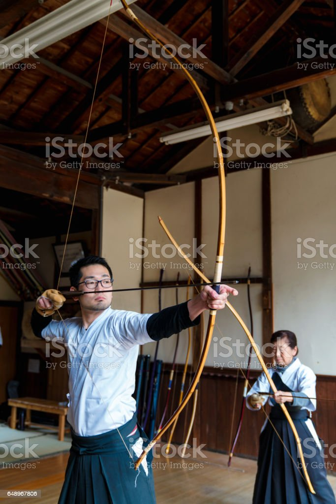 Archer draws his bow ready to shoot stock photo