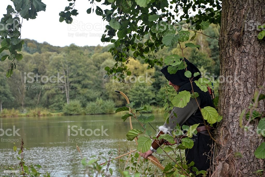 Archer  stands hidden behind tree with tense curve stock photo
