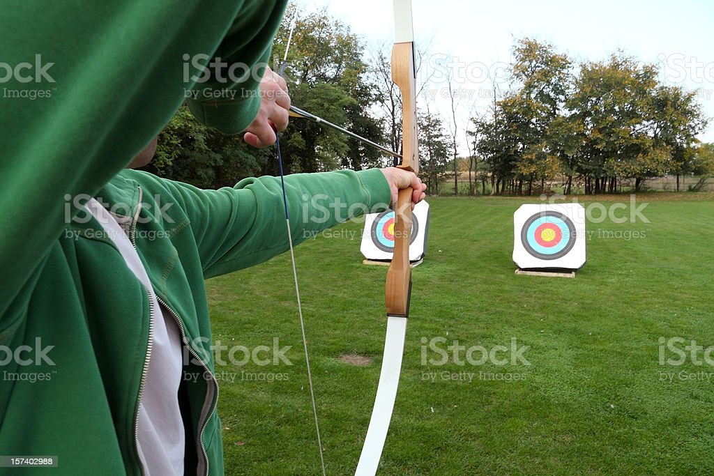 Archery firing at targets on a grass field stock photo