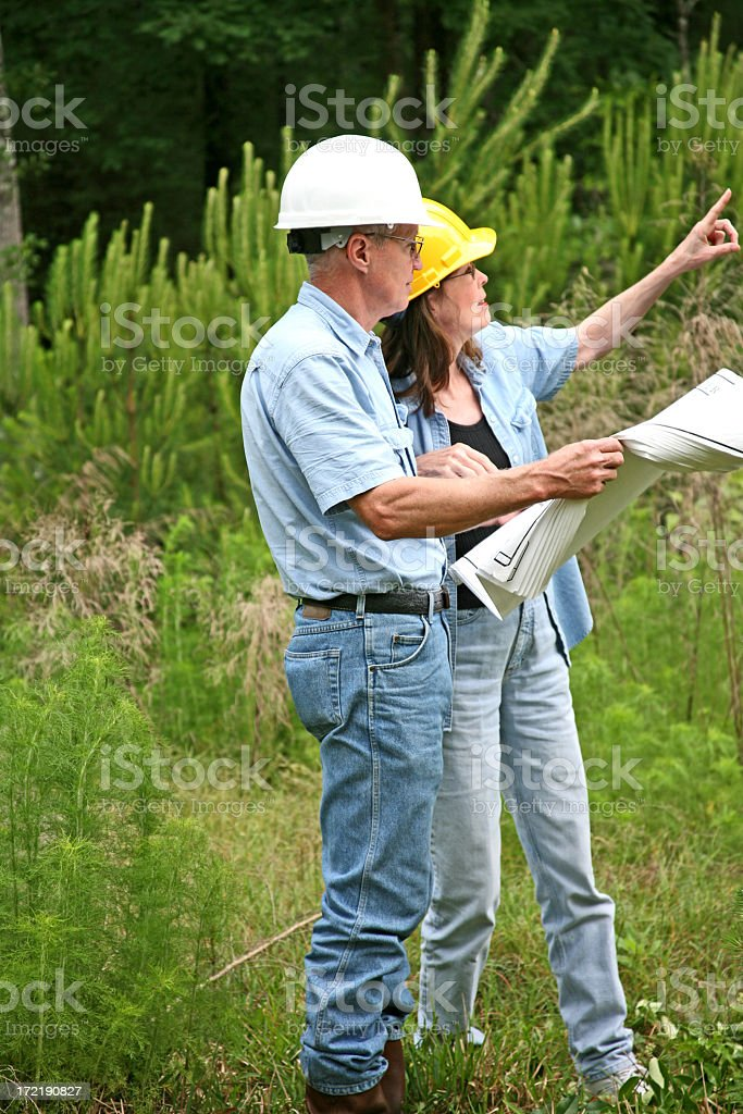 Architect and builder or surveyors discuss building location. Blueprints. stock photo