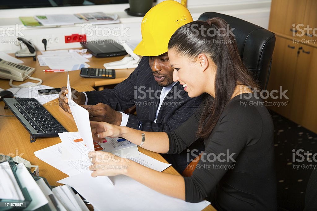 Architect and building engineer reviewing blueprints royalty-free stock photo