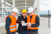 Architect and construction worker looking blueprint on tablet