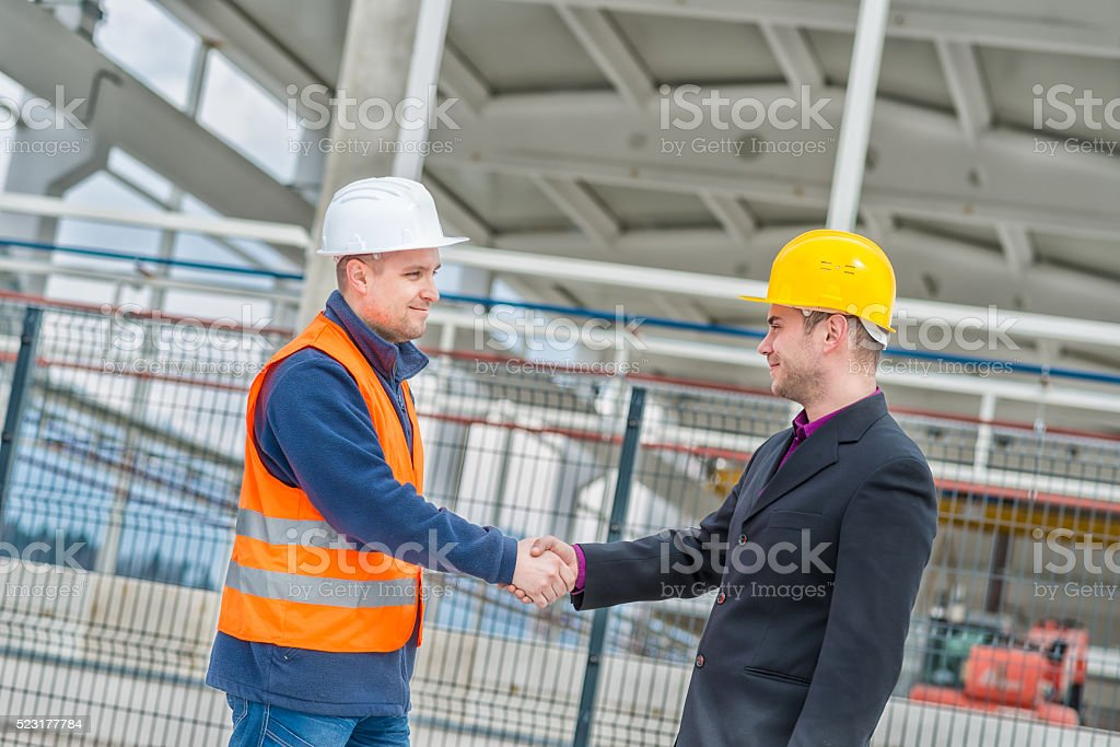 Architect and construction worker shaking hands stock photo