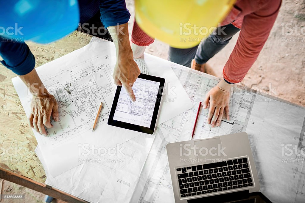 architect and construction worker with plans tablet pc and laptop