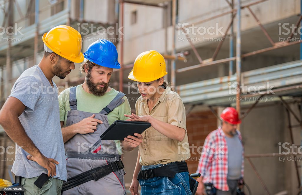 Architect And Construction Workers Reviewing Plans stock photo