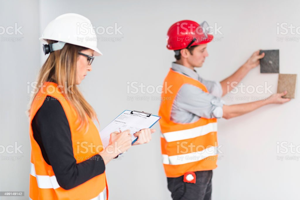 Architect and engineer examining wall tiles stock photo