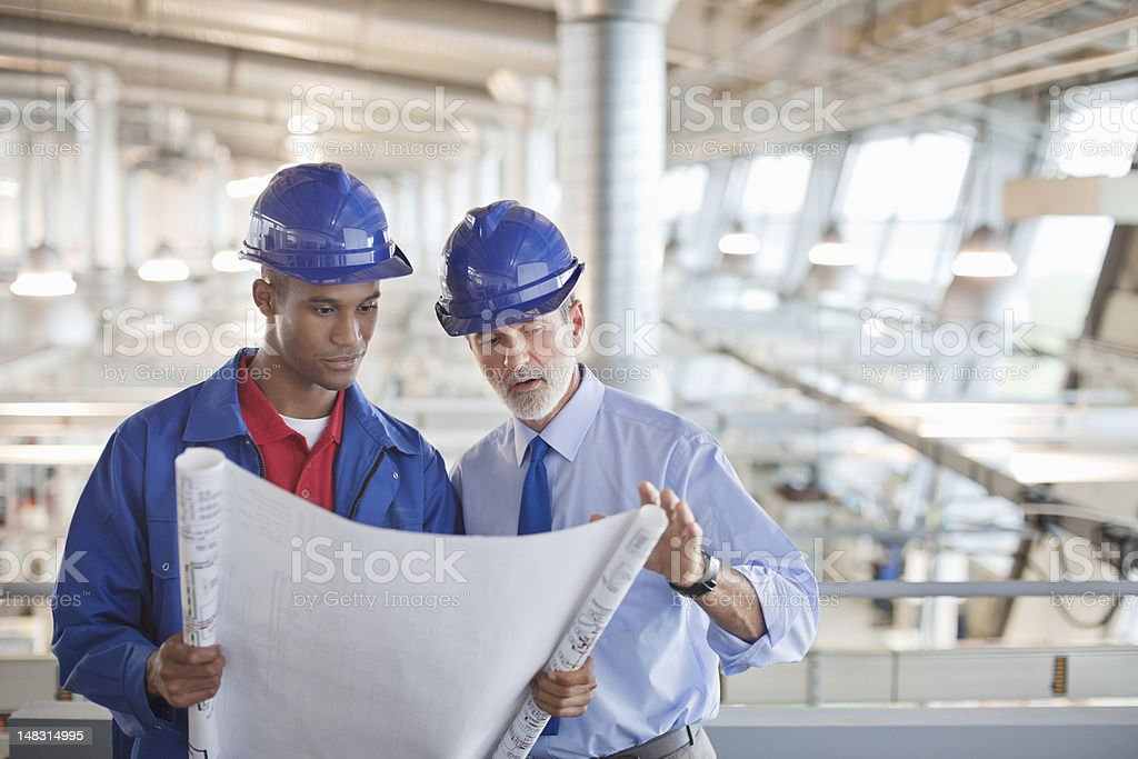 Architect and engineer reviewing blueprint in factory royalty-free stock photo