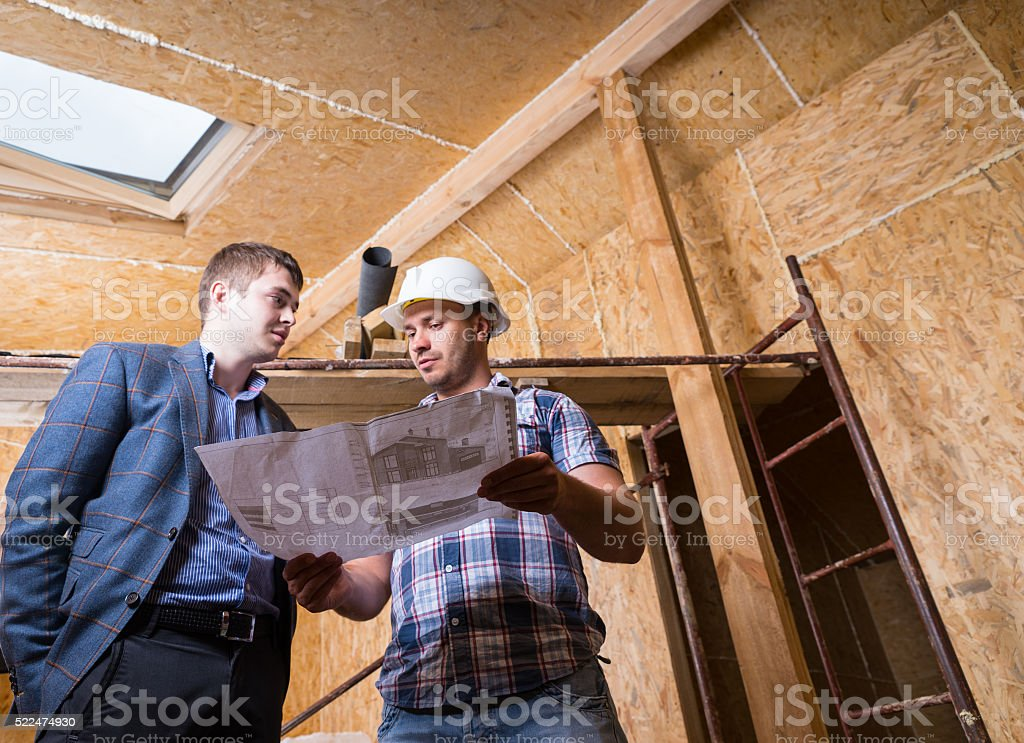 Architect and Foreman Consulting Building Plans stock photo