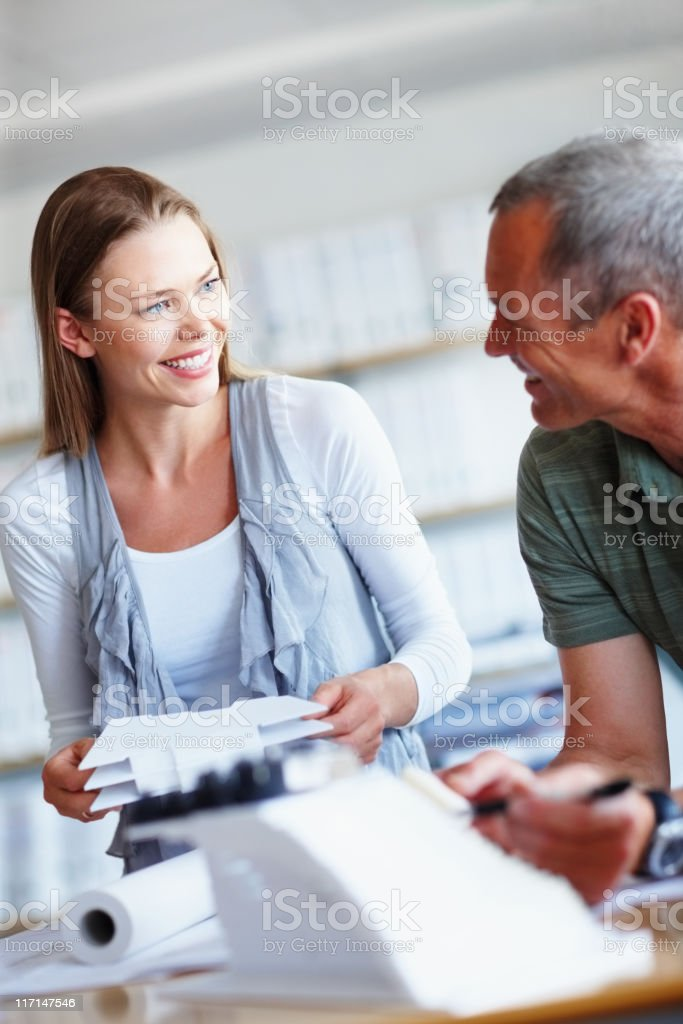 Architect and happy female client looking at house plans royalty-free stock photo