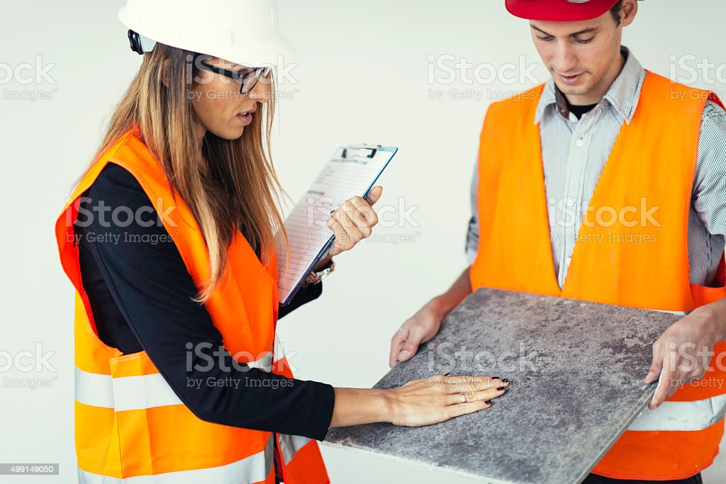 Architect at construction site, examining tiles stock photo