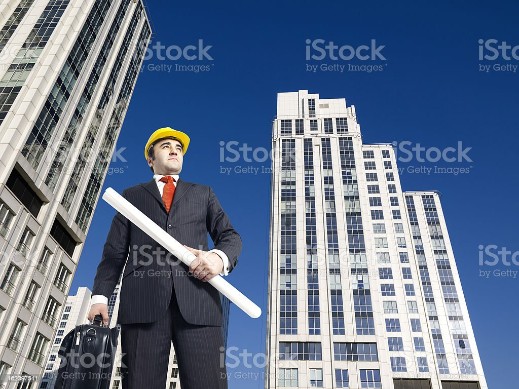 Architect at construction site, holding blueprint royalty-free stock photo