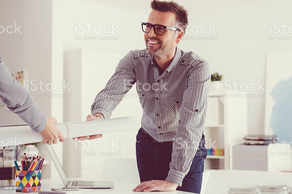 Architect at work in an office, holding blueprint stock photo