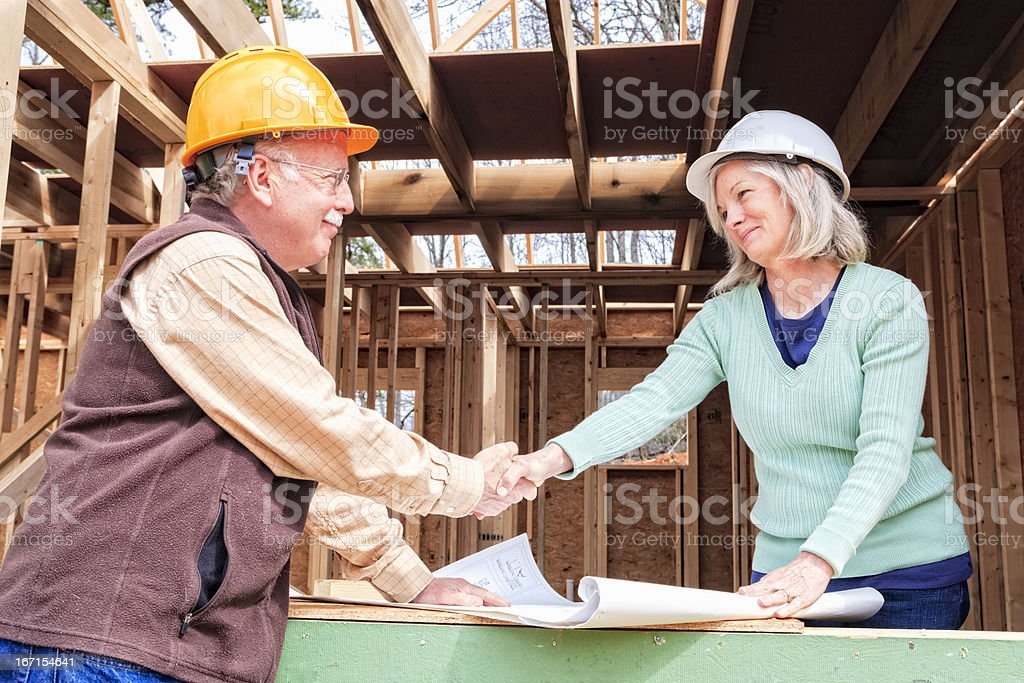 Architect, contractor, owner, man, woman at construction site royalty-free stock photo