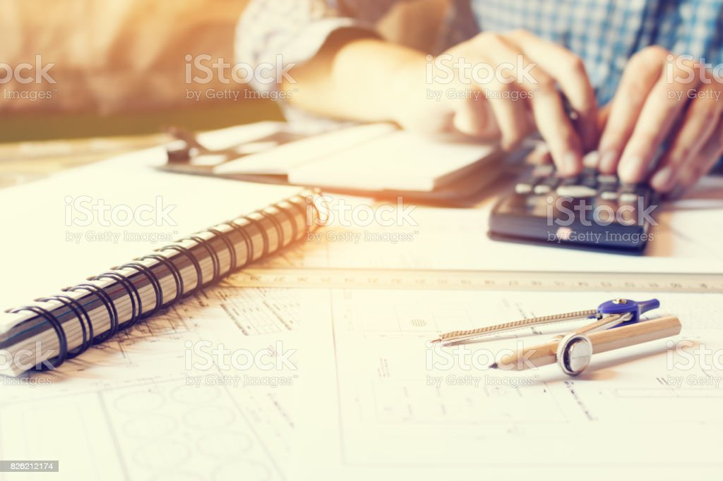 Architect engineer man calculate building area with equipment on desk at home office. stock photo