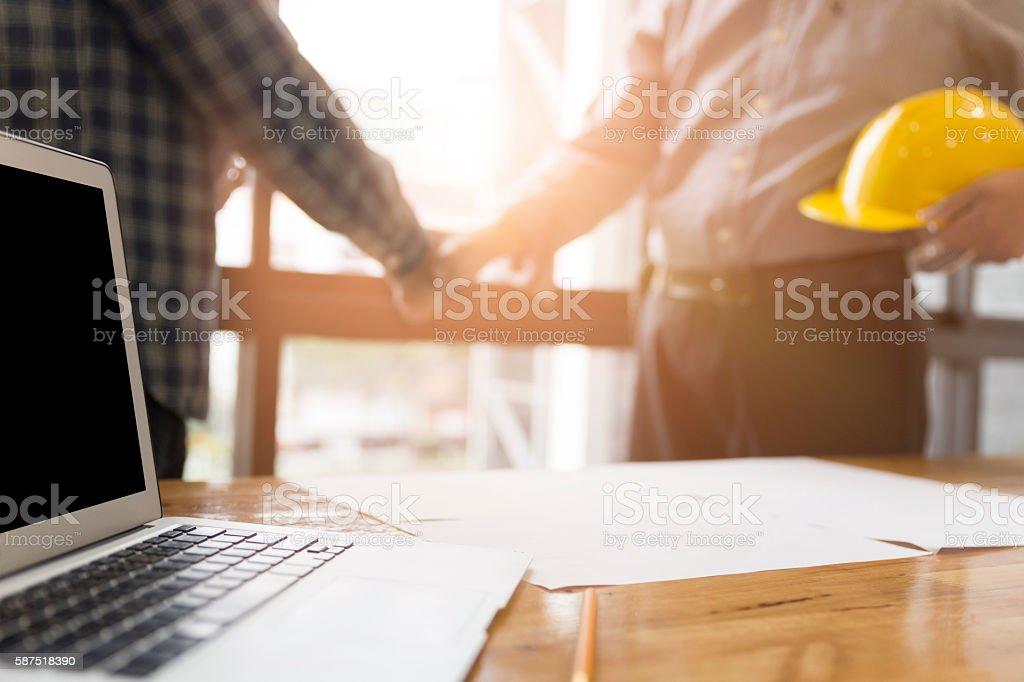 architect engineer shaking hands beside window - business stock photo