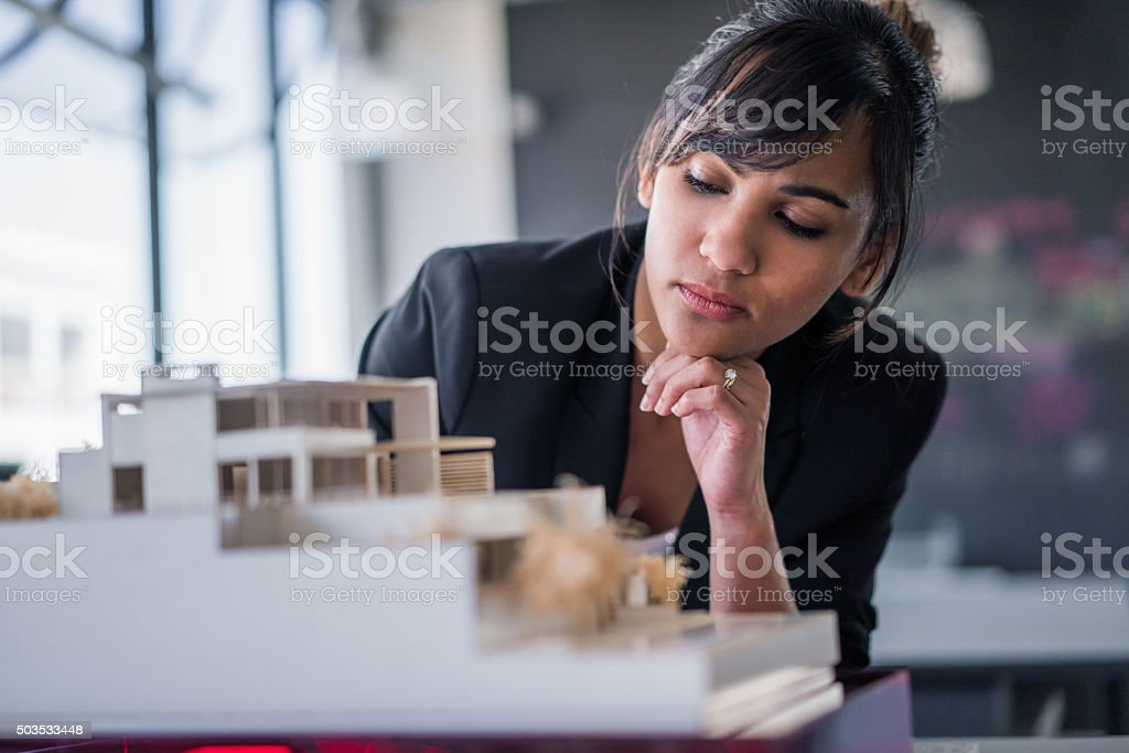 Architect examining artificial model at workplace stock photo
