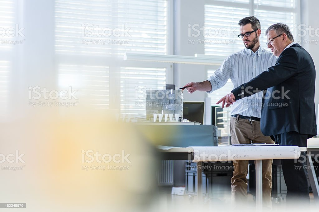 Architect explaining architectural model to client stock photo
