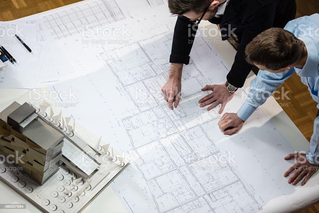 Architect explaining blueprint to client stock photo