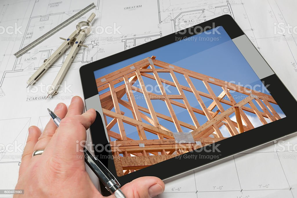 Architect Hand on Tablet Showing Home Framing Over House Plans stock photo