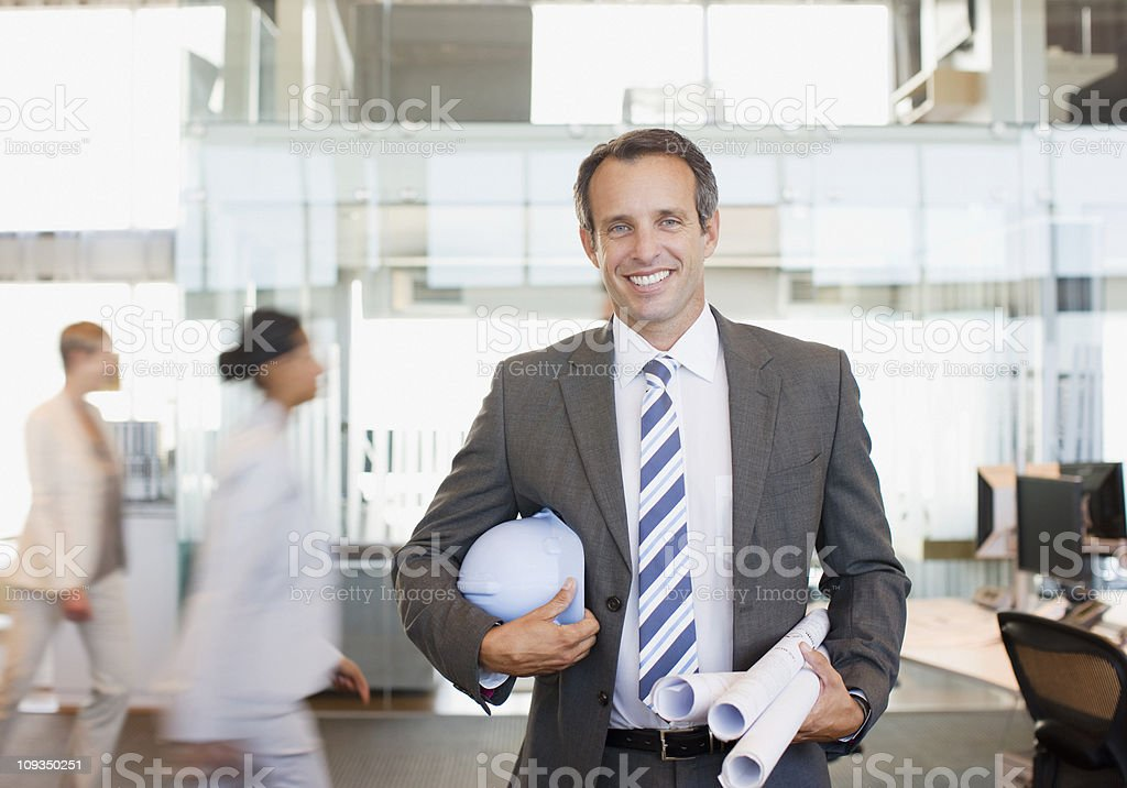 Architect holding blueprints in busy office stock photo