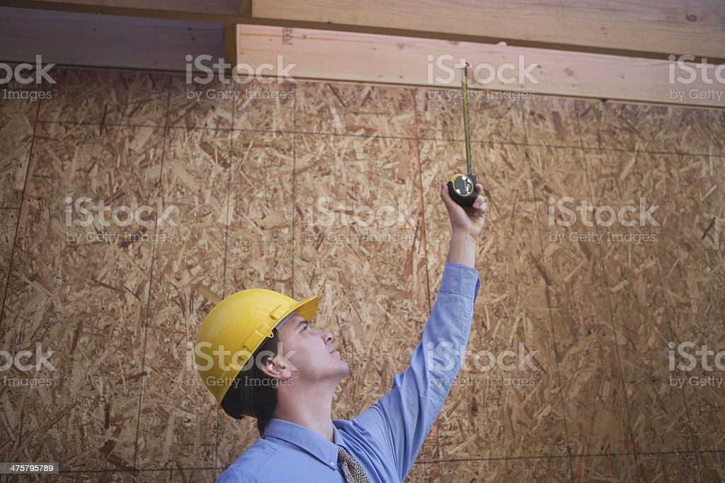 Architect Inspecting Framework With Measure Tape royalty-free stock photo
