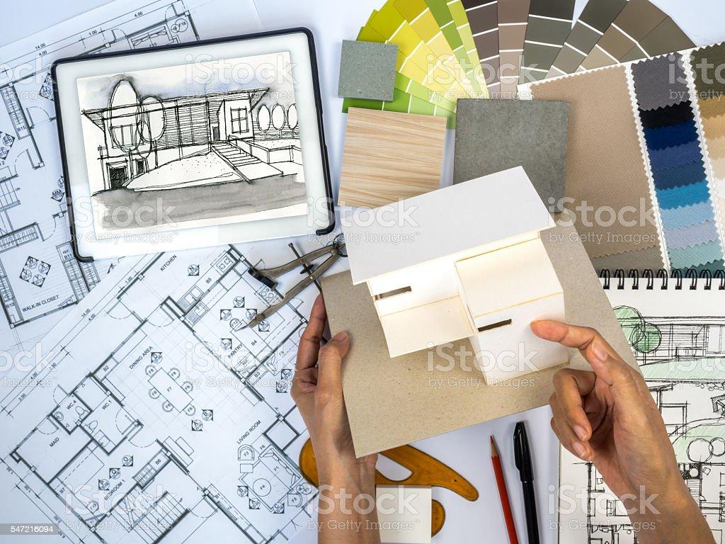 elegant architect interior designer working at worktable with home model royaltyfree stock photo with interior designers work - How Interior Designers Work