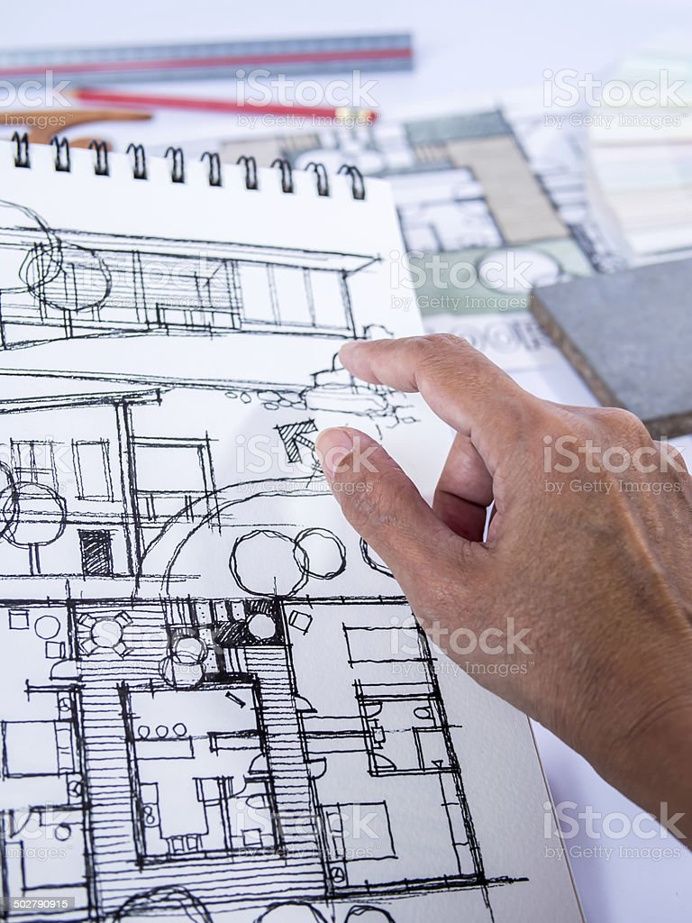 Architect /interior's hand working with illustration of home renovation stock photo