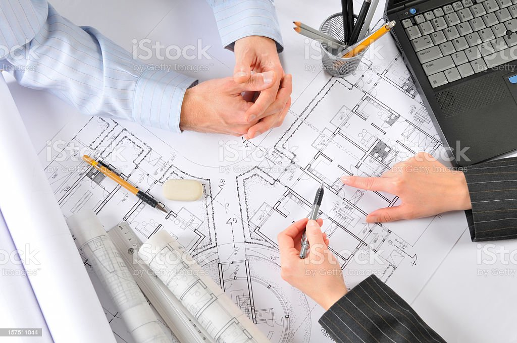 Architect is consulting with the client building plans, directly above royalty-free stock photo