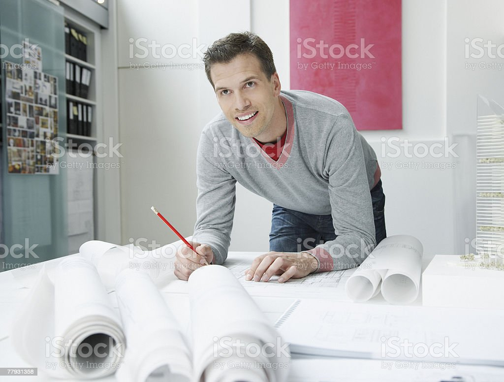 Architect leaning over table with drafts on it royalty-free stock photo