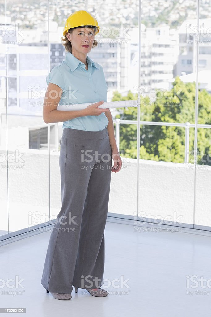 Architect looking at camera with blueprint wearing helmet royalty-free stock photo