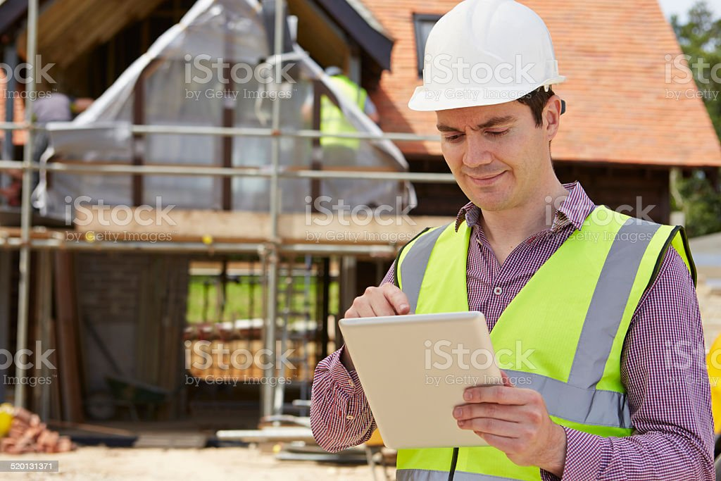 Architect On Building Site Using Digital Tablet stock photo