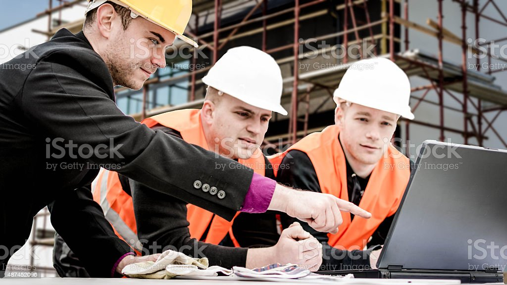 Architect pointing plans on laptop stock photo