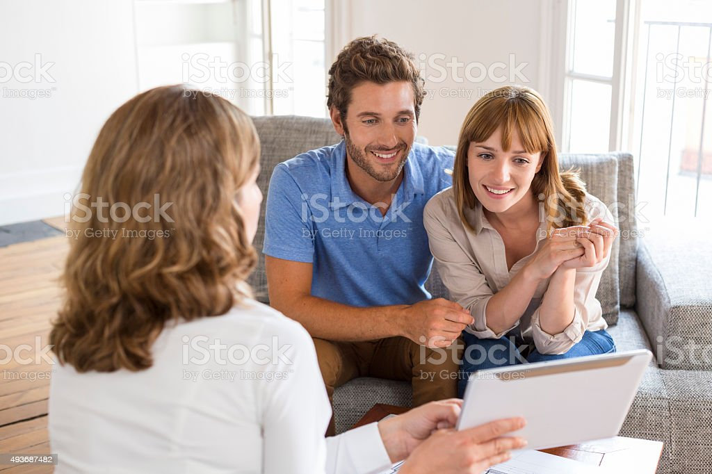 Architect presenting a new project on tablet to a couple stock photo