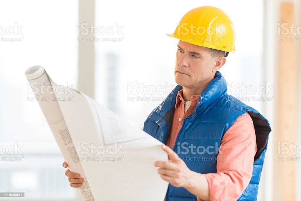 Architect Reading Blueprint At Construction Site royalty-free stock photo
