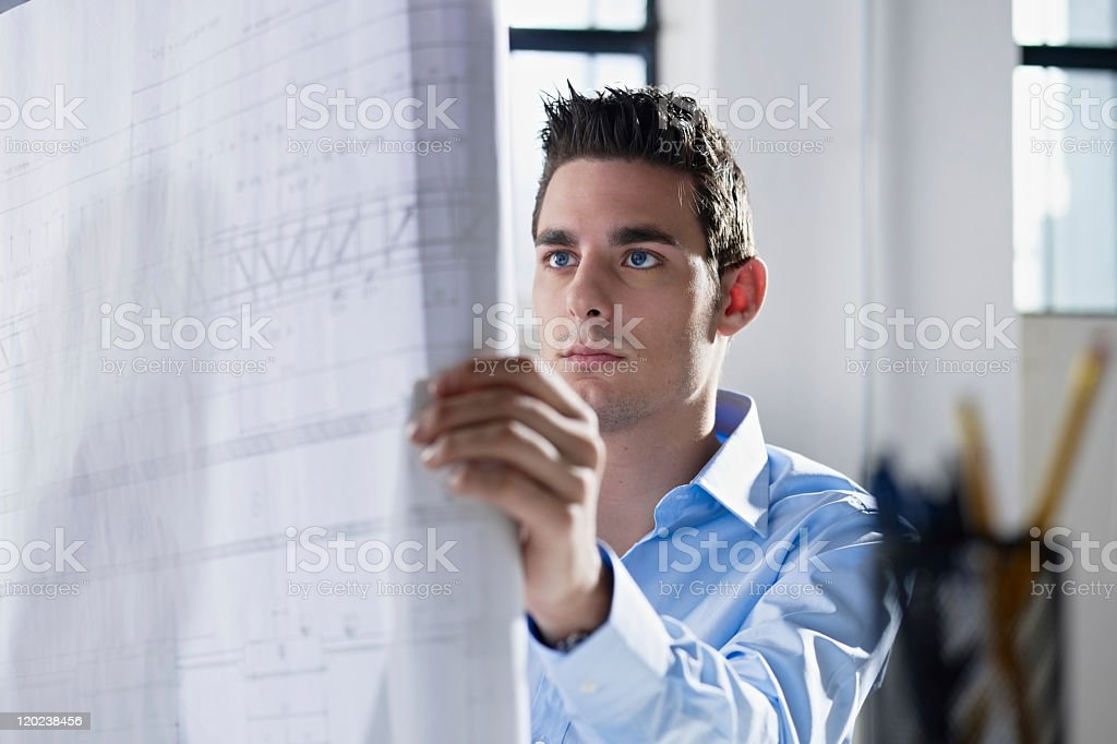 Architect reading large blueprint in an office  royalty-free stock photo