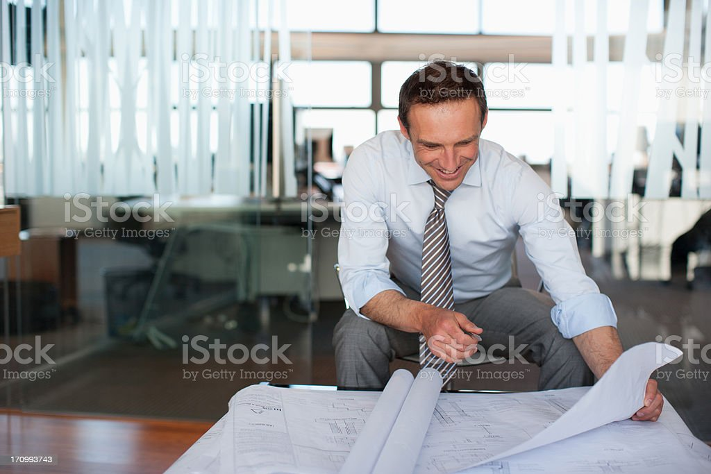 Architect reviewing blueprints in office stock photo