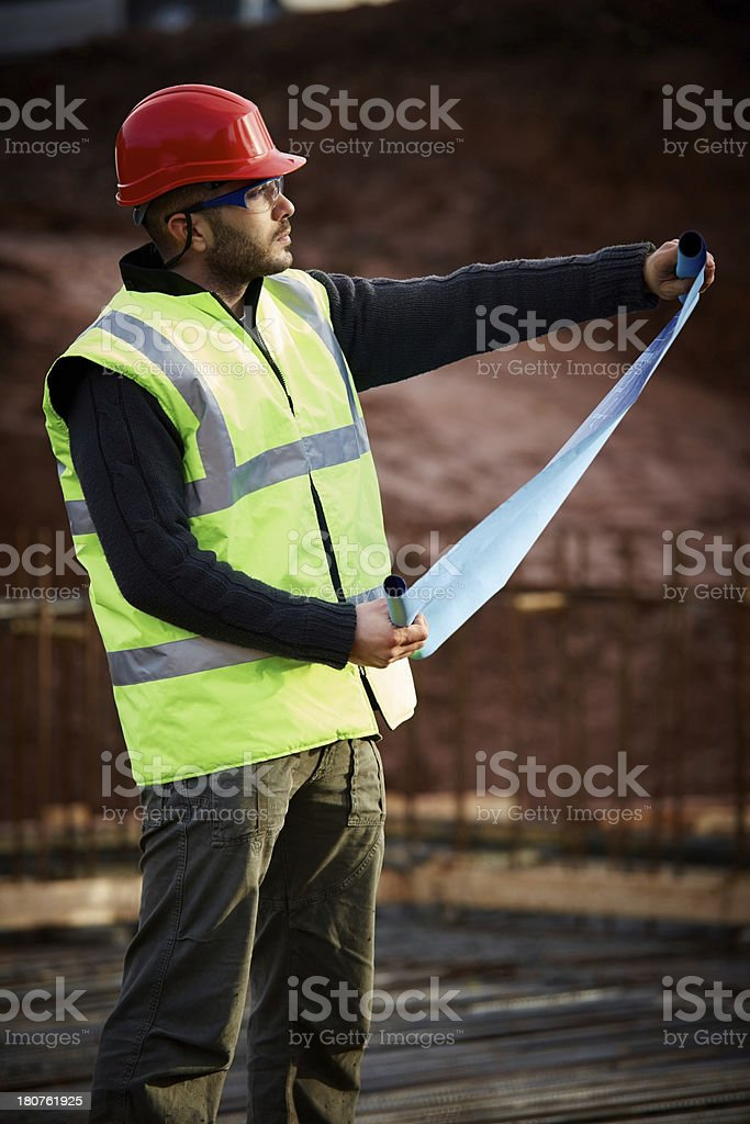 Architect reviewing construction plan at work site royalty-free stock photo