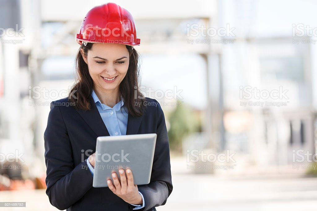 Architect reviewing plans on digital tablet at construction site stock photo
