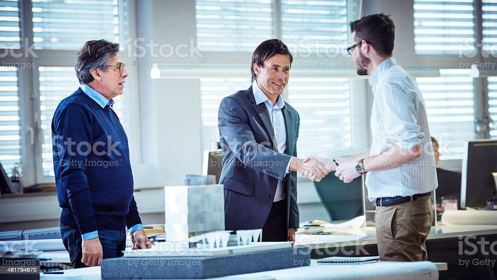Architect shaking hand with client stock photo
