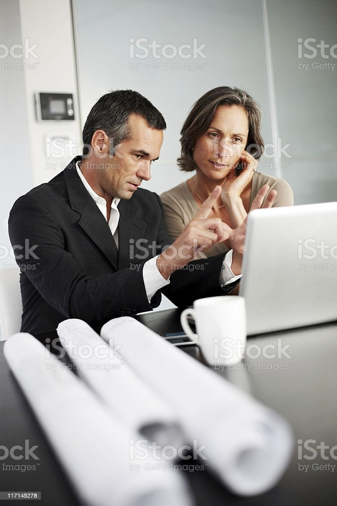 Architect showing and explaining plans to female client royalty-free stock photo