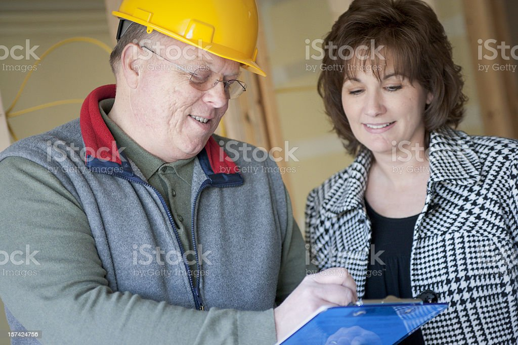 Architect showing woman blue prints of his work royalty-free stock photo